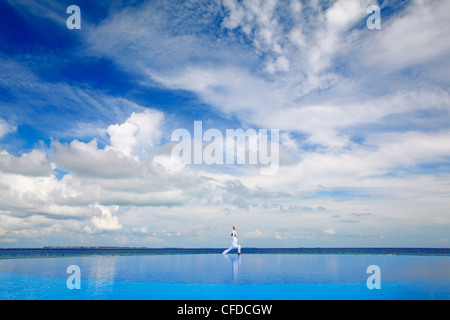 Young man meditating by infinity pool, Maldives, Indian Ocean, Asia - Stock Photo