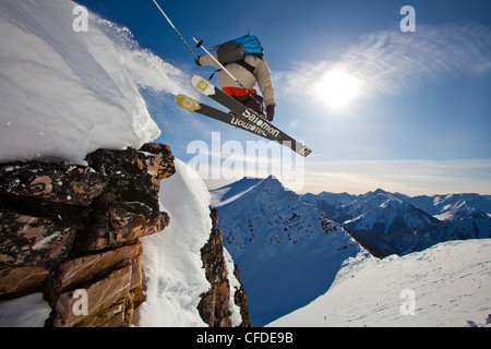 A young male skier airs a cliff in the kicking horse backcountry, Golden, Britsh Columbia, Canada - Stock Photo