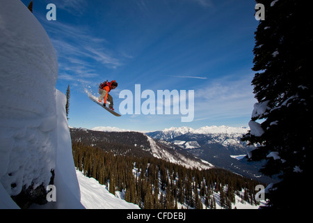 A snowboarder airs off a snow pillow while on a cat ski trip. Monashee Mountains, Vernon, Britsh Columbia, Canada - Stock Photo