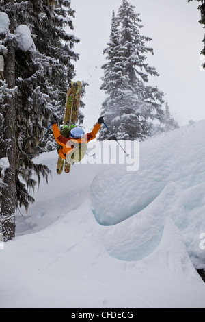 A male skier airs off a snow pillow while on a cat ski trip. Monashee Mountains, Britsh Columbia, Canada - Stock Photo