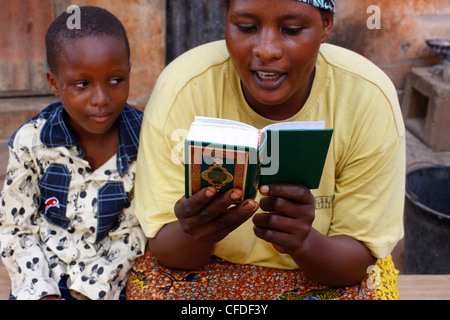 African mother reading the Koran, Lome, Togo, West Africa, Africa - Stock Photo