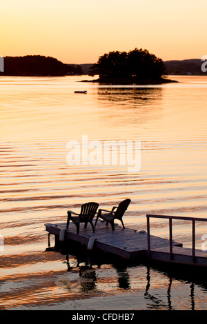Lawn chairs on wharf at sunset, LaHave River, Nova Scotia, Canada - Stock Photo