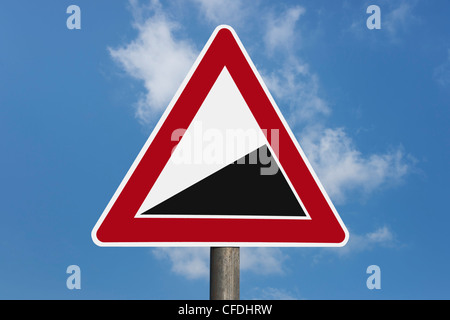 Detail photo of a danger sign 'Upward gradient' without inscription, background sky. - Stock Photo