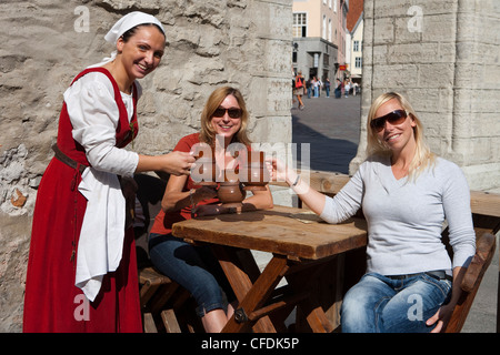 Waitress in medieval costume and tourists with mugs of beer at Olde Hansa restaurant in Town Hall Square (Raekoja - Stock Photo