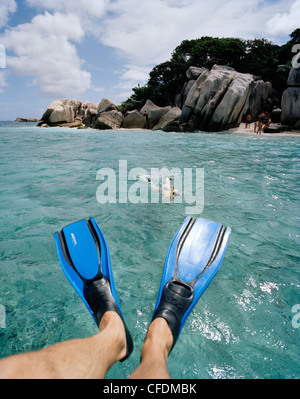 Snorkelling in shallow water over coral reef near tiny Coco Island, La Digue and Inner Islands, Republic of Seychelles, - Stock Photo