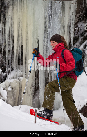 A young woman snowshoeing in fresh powder in the eastern townships on Mt. Ham, Quebec, Canada - Stock Photo