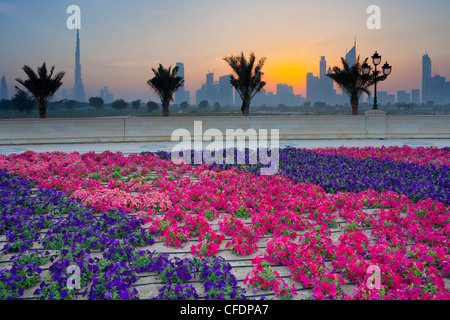 Flowers and palm trees in front of skyline at sunset, Dubai, United Arab Emirates, UAE, Asia - Stock Photo
