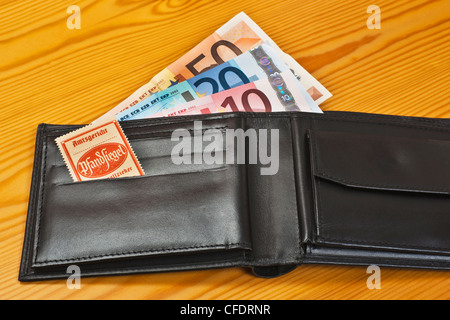 An open purse with Euro Banknotes, inside is a bailiff's seal for distraint of goods. - Stock Photo