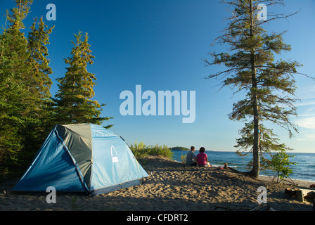 Couple with tent on beach, Agawa Bay, Lake Superior Provincial Park, Ontario, Canada - Stock Photo