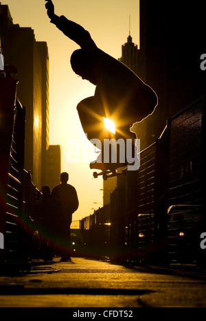 A skateboarder does an 'ollie' along a street in downtown Toronto at sunset, Ontario, Canada. - Stock Photo