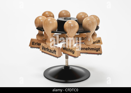 many stamps with different inscriptions in German language hanging in a stamp rack, background white. - Stock Photo