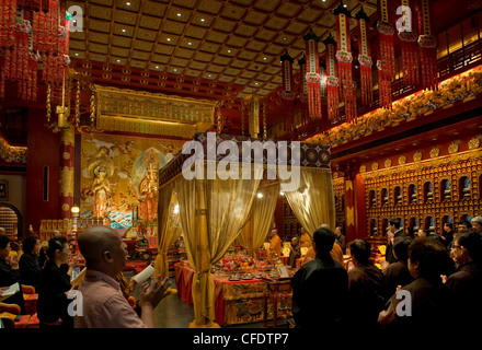 Chanting in the Hundred Dragons hall in the Buddha Tooth Relic temple in Singapore, Southeast Asia, Asia - Stock Photo