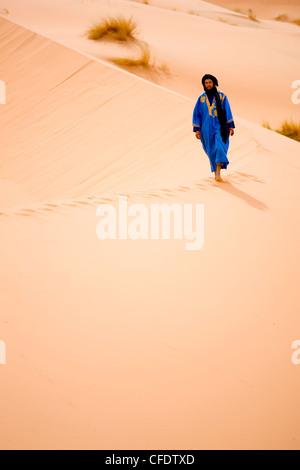 Berber man in blue robe walking along the ridge of a sand dune in the Erg Chebbi sand sea near Merzouga, Morocco, - Stock Photo
