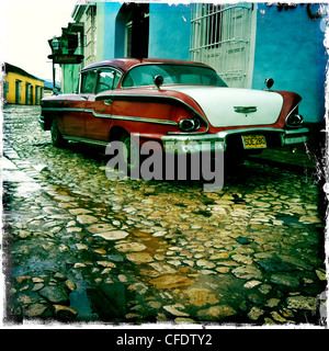 Old American car parked on a cobbled street in the town of Trinidad, Cuba, West Indies, Central America - Stock Photo