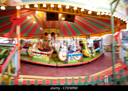 Children riding a carousel, Hyde Park, London, England, United Kingdom, Europe (blurred motion) - Stock Photo