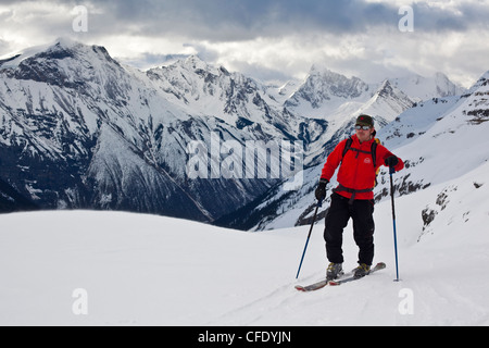 A man on a backcountry ski tour in the early morning light. Icefall Lodge, Golden, British Columbia, Canada - Stock Photo