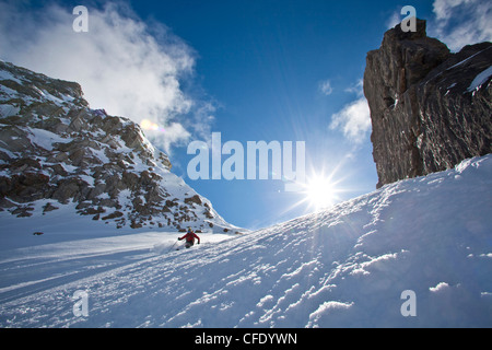 A woman skis fresh powder while on a backcountry hut trip at Icefall Lodge, British Columbia, Canada - Stock Photo
