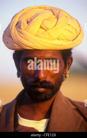 A Rajasthani man poses for the camera at the Pushkar Camel Fair in Pushkar, Rajasthan, India - Stock Photo
