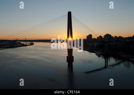 Sunset behind the Skytrain Bridge and the Fraser River in New Westminster, British Columbia, Canada. - Stock Photo