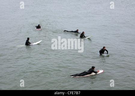 A group of surfers waiting to catch a wave next to Bournemouth Pier - Stock Photo