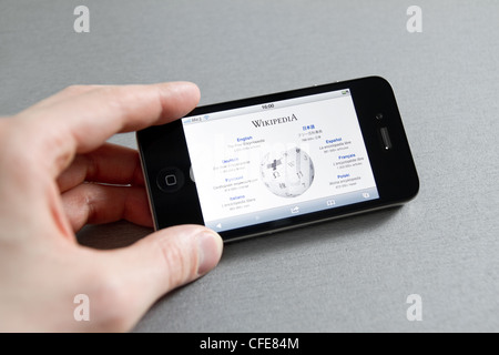 Man hand holding Apple iPhone with Wikipedia start page on a screen. - Stock Photo