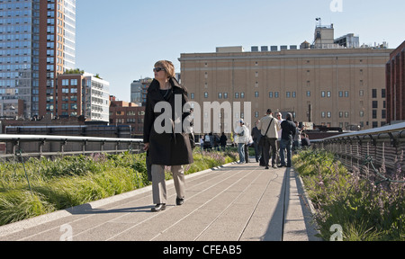 A woman walks along a path on The High Line in New York City. - Stock Photo