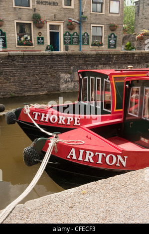 Front of 2 bright red canal boats (names on bow) moored side by side by towpath & canalised pub - Leeds-Liverpool - Stock Photo