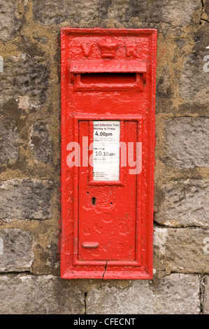 Bright red iconic historic wall-mounted Victorian VR post box set into stone wall (close-up, front view) - Leathley, - Stock Photo