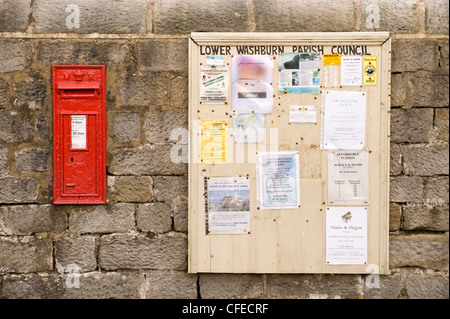 Bright red wall-mounted Victorian post box, parish council noticeboard on stone wall & notices for community info - Stock Photo