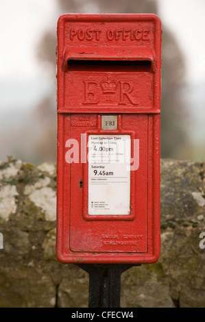 Close-up front view of bright red post box (lamp box style, marked ER) standing in front of drystone wall - Leathley, - Stock Photo