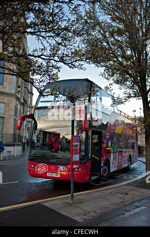 A double decker bus waits in evening sunshine at a bus stop in Bath, UK - Stock Photo