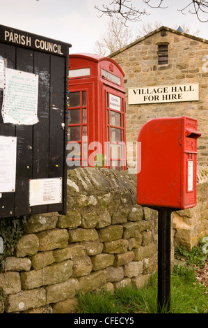 A noticeboard, red post box and a K6 telephone box stand together in a North Yorkshire village in front of the village - Stock Photo