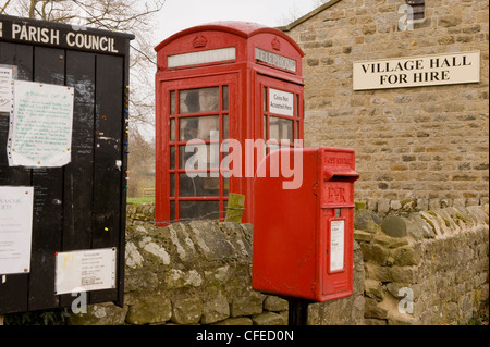 Street furniture - parish noticeboard, red post box & iconic K6 telephone box by village hall (for hire sign) - - Stock Photo
