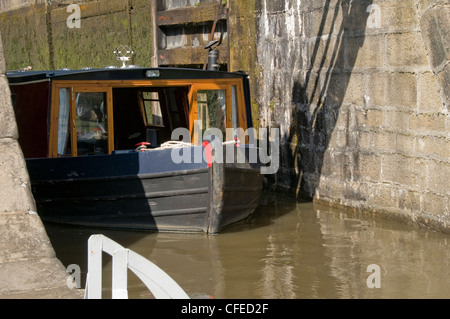 Bow (front) of narrowboat sailing & navigating out of bottom lock of The Five Rise Locks - Bingley, Leeds Liverpool - Stock Photo
