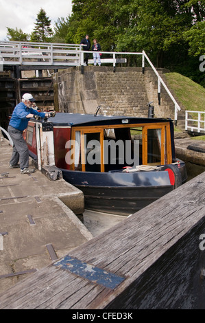 Narrowboat in lock chamber passing through The Five Rise Locks on Leeds Liverpool Canal (man winding handles to - Stock Photo