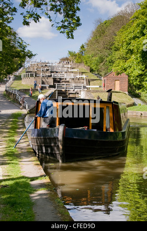 Man on board narrowboat using pole to push away from canal bank   (scenic Five Rise Locks beyond) - Leeds Liverpool - Stock Photo