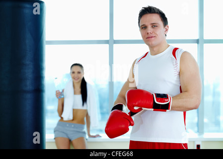 Portrait of young man in red boxing gloves looking at camera in gym - Stock Photo