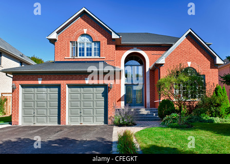 Brick house in suburbs with two car garage - Stock Photo