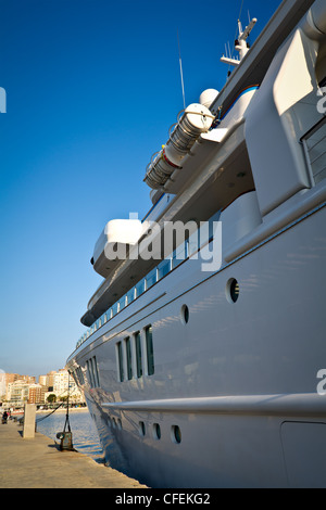 Large yacht docked in port under blue sky - Stock Photo
