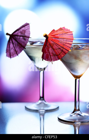 Cocktail glasses with umbrellas and holiday lights in the background - Stock Photo