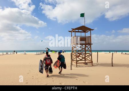 Green flag on coastguard lookout on Atlantic coast sandy beach with people kite surfing Praia de Chaves Boa Vista - Stock Photo