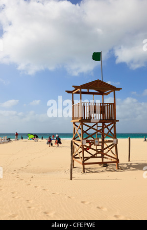 Green flag on coastguard lookout on sandy beach on Atlantic coast Praia de Chaves Boa Vista Cape Verde Islands - Stock Photo
