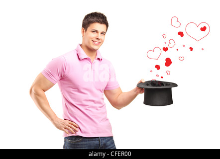Smiling man holding a top hat and hearts coming out isolated on white background - Stock Photo