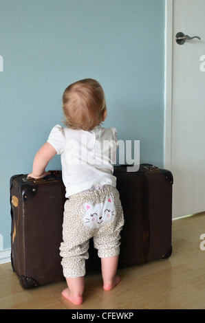 Toddler holding a suitcase - concept photo - leaving home at a young age - Stock Photo