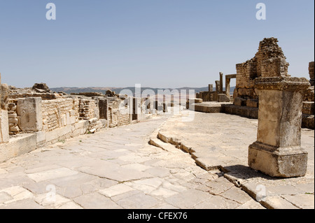 Dougga. Tunisia. View of an ancient Roman stone paved street that cuts through the city. Dougga is wonderfully intact - Stock Photo