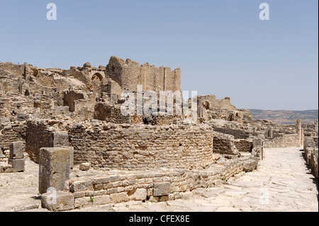Dougga. Tunisia. View of an ancient Roman stone paved street that cuts through the city. In the far left is the - Stock Photo