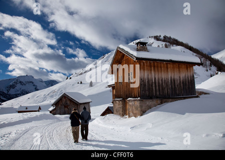 Winter walk on snowy path through wooden barns around San Pellegrino Pass, Dolomites, Alps, Trentino Alto Adige, - Stock Photo