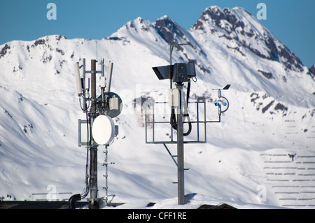 Communication tower with lifecam, satellite dishes and aerials in skiing resort in Montafon, Austria - Stock Photo