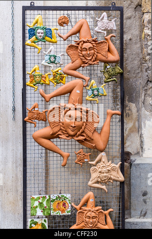 Shop display showing terracotta representations of the ancient symbol of Sicily, the triskelion or trinacria - Stock Photo