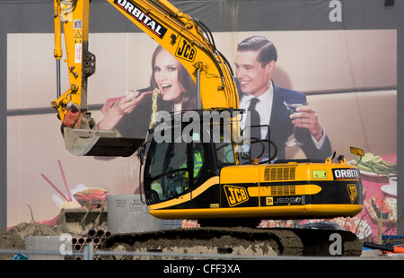 JCB excavator and aspirational poster on wall during building of 2012 Olympic Westfield City shopping centre, Stratford. - Stock Photo
